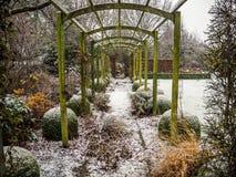 Деревянная структура перголы во время зимы в снеге покрыла сад стоковые изображения rf