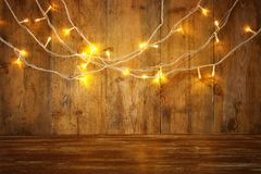 Деревянная таблица доски перед гирляндой золота рождества теплой освещает на деревянной деревенской предпосылке верхний слой ярко Стоковые Изображения