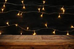 Деревянная таблица доски перед гирляндой золота рождества теплой освещает на деревянной деревенской предпосылке Стоковые Фотографии RF