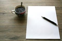 Деревянная таблица стола офиса с чистым листом бумаги, ручкой пересекла и чашка стоковые фотографии rf