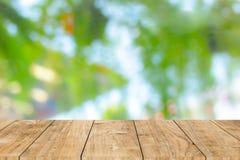 Деревянная таблица с предпосылкой нерезкости зеленой стоковые фото