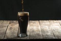 Деревянная таблица с черными предпосылкой и пивом ремесла Стоковые Фотографии RF