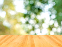 Деревянная таблица и зеленая предпосылка природы bokeh Стоковая Фотография