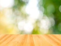Деревянная таблица и зеленая предпосылка природы bokeh Стоковые Изображения RF