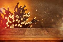 Деревянная таблица доски перед гирляндой золота рождества теплой освещает на деревянной деревенской предпосылке Стоковые Изображения RF