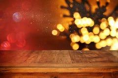 Деревянная таблица доски перед гирляндой золота рождества теплой освещает на деревянной деревенской предпосылке Стоковое Изображение