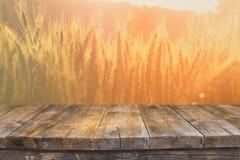 Деревянная таблица доски перед полем пшеницы на свете захода солнца Подготавливайте для монтажей дисплея продукта Стоковое Фото