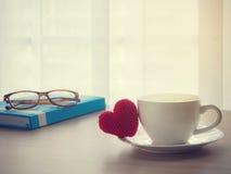 Деревянная таблица офиса с красным знаком формы сердца на чашке coff latte Стоковое Изображение RF