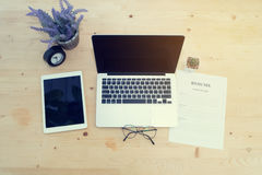 Деревянная таблица офиса с пустым экраном на компьтер-книжке, таблетке, фиолетовом Ла Стоковая Фотография