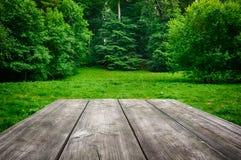 Деревянная таблица с зеленой предпосылкой природы Стоковая Фотография RF