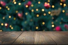 Деревянная темная столешница и запачканное bokeh рождественской елки Предпосылка Xmas для дисплея ваши продукты стоковые фотографии rf