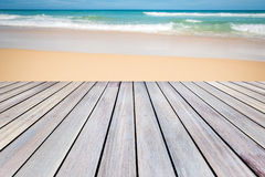 Деревянная терраса с предпосылкой пляжа песка Стоковые Изображения