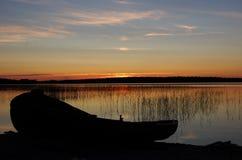 Деревянная шлюпка на озере захода солнца Стоковое фото RF