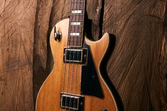 Деревянная электрическая басовая гитара на деревянной предпосылке Стоковое фото RF