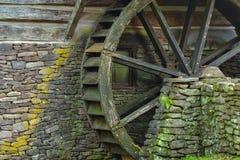 Деревянное колесо затвора воды и мшистые камни на стороне старой Стоковые Изображения RF