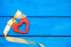 Деревянное сердце wwooden сердце с смычком на голубой предпосылке, день ` s валентинки романское украшение сярприз Стоковая Фотография RF