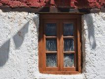 Деревянное старое окно с малыми стеклами на белой стене деревенского тибетского дома, тени от молитвы сигнализирует на поверхност Стоковые Изображения