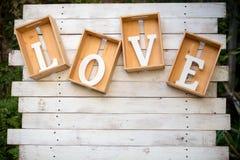 Деревянное слово ВЛЮБЛЕННОСТЬ алфавита в деревянной коробке стоковое фото rf