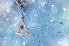 Деревянное украшение ели с серебряной ветвью ели на голубом backgr Стоковая Фотография