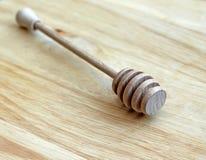 Деревянное drizzler меда на деревянной предпосылке Стоковая Фотография