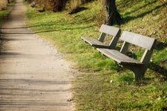 2 деревянной скамьи на пути в парке в солнце вечера, полисмене Стоковая Фотография RF