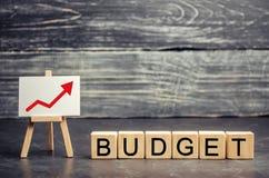 """Деревянные блоки и надпись """"бюджет """"и поднимающая вверх стрелка Концепция успеха в бизнесе, финансового роста и богатства Pr рост стоковое фото rf"""