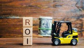 Деревянные блоки со словом ROI и деньги с грузоподъемником Коэффициент между чистым доходом и ценой вклада следующ из стоковая фотография rf