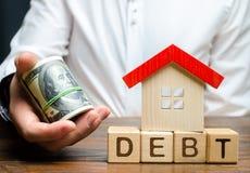 Деревянные блоки с задолженностью, домом и долларами слова в руках бизнесмена Концепция платежа в обусловленный срок задолженност стоковые фотографии rf