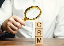Деревянные блоки с управлением и бизнесменом отношения клиента слова CRM Стратегии автоматизации для взаимодействовать с стоковое изображение