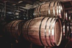 Деревянные бочонки с вискиом в темном погребе стоковые фото