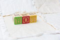 Деревянные блоки алфавита на мальчике правописания лоскутного одеяла далеко Стоковые Фото