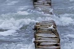 Деревянные волнорез и волны с пеной на море Стоковая Фотография RF