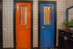 Деревянные двери старой ванной комнаты дома Голубые и красные дверь и зеркало над washbasin Стоковые Фотографии RF