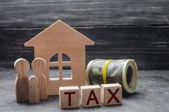 Деревянные диаграммы семьи стоят около деревянных дома и денег Налог на собственность Оплата налогов к положению Законопослушный  Стоковые Изображения