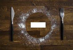 Деревянные диски темного коричневого цвета предпосылки объезжают прямоугольник бумаги листа вилки ножа приправой перца соли моря  стоковое изображение rf