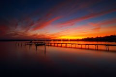 Деревянные док и рыбацкая лодка на озере, съемка захода солнца Стоковая Фотография RF