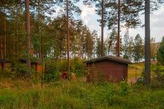 Деревянные дома в лесе озером на заходе солнца Стоковые Изображения