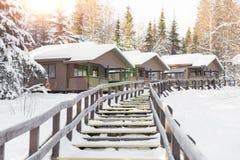 Деревянные дома в покрытой снег зиме леса отдыхают Стоковое фото RF