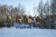 Деревянные дома, загоренные заходящим солнцем, среди леса березы Стоковые Фото