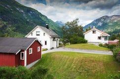 Деревянные дома, зеленые цвета и голубая предпосылка облака стоковые изображения
