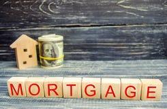 Деревянные дом и доллары Деревянные блоки и ` ипотеки ` надписи кредит для свойства афоризмов Ссуды деловому предприятию для реал стоковые изображения rf