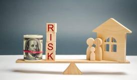 Деревянные дом и кубы со стойкой риска и семьи слова в масштабах Концепция риска, потери недвижимости Свойство insurance стоковые изображения