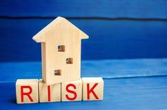 Деревянные дом и кубы с риском слова Концепция риска, потери недвижимости Свойство insurance Займы обеспеченные домом, ap стоковое фото rf