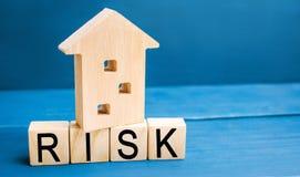 Деревянные дом и кубы с риском слова Концепция риска, потери недвижимости Свойство insurance Займы обеспеченные домом, ap стоковая фотография rf