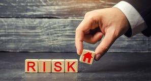 Деревянные дом и кубы с риском слова Концепция риска, потери недвижимости Свойство insurance Займы обеспеченные домом, ap стоковое изображение rf