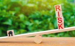 Деревянные дом и кубы с риском слова на масштабах Концепция риска, потери недвижимости Свойство insurance Одалживает secur стоковая фотография