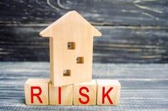 деревянные дом и кубы с ` слова рискуют ` Концепция риска, потери недвижимости Свойство insurance Займы обеспеченные домом, стоковая фотография rf