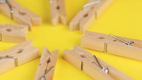 Деревянные естественные бамбуковые зажимки для белья на желтой предпосылке акции видеоматериалы