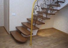 Деревянные лестницы и tracery металла выковали перила Стоковое Фото