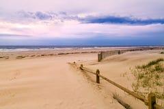 Деревянные загородка и песчаный пляж Стоковое Изображение